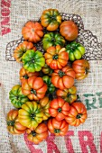 VArious beefsteak tomatoes on a piece of jute (seen from above)