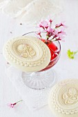 A Springerle (anise biscuits with an embossed design) balanced on the edge of a glass of strawberry wine