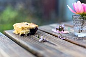 A slice of berry cake on a wooden table