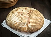 A freshly baked homemade loaf of wheat sourdough bread on a wooden table