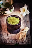 Matcha tea powder in a ceramic pot with tea bowls and a bamboo whisk
