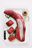 Beef fillet with thyme, a knife and kitchen twine on a tray