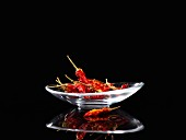 Dried chilli peppers in a glass dish against a black background