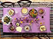 Blick von Oben auf frühlingshaft gedeckten Tisch mit pikanten & süssen Gerichten