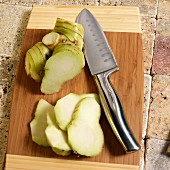 Galanga root, whole and sliced, on a chopping board with a knife