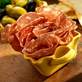 Sopressata in a yellow dish with green and black olives and crackers