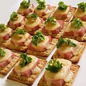 Crackers with ham, Swiss cheese, mustard and chervil