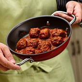 A man holding a pan of meat balls in tomato sauce