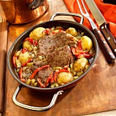 Roast beef with potatoes, peppers, and onions in a pan (Brazil)