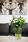 Gartenblumen in Glasvase und Alvar Aalto-Windlichter auf Tisch, im Hintergrund Bild über Sofa