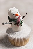 A snowman cupcake with icing sugar for Christmas