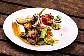 A lamb chop served with Mediterranean vegetables