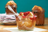 A peanut muffin with raspberry jam in a jar with a bite taken out