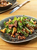 Rocket salad with beef strips, chanterelle mushrooms and pecan nuts