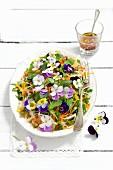 Vegetable salad (kohlrabi, yellow pepper, carrots, rocket) with parsley, basil and pansies