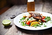 Grilled Cajun salmon steak on a bed of potato wedges and rocket and tomato salad with Parmesan