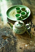 A light green oriental tea service on an old wooden surface