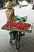A Vietnamese person transporting a crate of tomatoes on a bicycle
