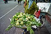 Vietnamesin transportiert Korb mit Zimtäpfeln auf dem Fahrrad