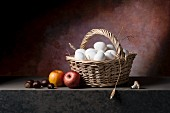 Fresh eggs in a wicker basket with apples, chestnuts and mushrooms