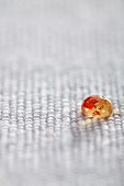 Molecular gastronomy: a droplet of jelly with chilli on a piece of coarse fabric