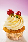A cupcake topped with buttercream and decorative toadstools