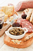 A platter of cheese and cured meats with cocoa pesto, figs and grissini