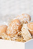 Painted Easter eggs on straw in box
