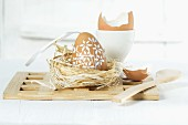 An Easter egg in straw nest with a wooden spoon