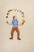 A man juggling with fruit and vegetables