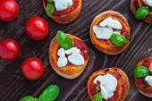 Pizzette (mini pizzas with tomatoes, mozzarella and basil)