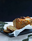 Sliced honey-nut loaf cake with orange syrup and baking paper on a chopping board