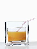 Apricot juice with a straw in a thick glass