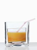 Aprikosensaft mit Strohalm in dickwandigem Glas
