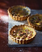 Three hazelnut tartlets with icing sugar