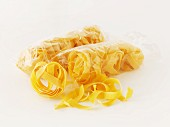 Tagliatelle in a cellophane bag on a white surface