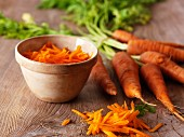 Fresh organic carrots next to a bowl of grated carrots