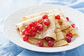 Pancakes with redcurrants and icing sugar