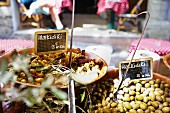 Olives in large bowls with signs at a market