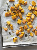 Roasted diced squash with herbs on a baking tray