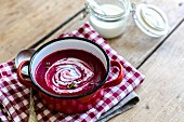 Bowl of Beet Soup with a Dollop of Sour Cream Garnished with Fennel; From Above