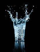 A splashing glass water against a black background