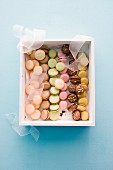 Various colourful macaroons in a gift box (seen from above)