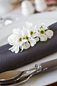 Place setting with a grey napkin and fruit blossoms