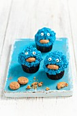 Monster muffins decorated with blue cream and almond biscuits