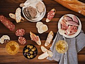 A charcuterie board featuring bread, duck, foie gras, olives and white wine