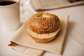 A sesame bagel with a cup of coffee and a newspaper