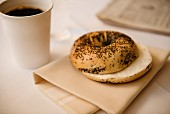 A poppy seed bagel with a cup of coffee and a newspaper