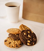 Various cookies with a cup of coffee and a paper bag in the background