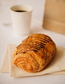 A French pastry with chocolate drizzle and a cup of coffee and a paper bag in the background